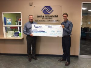Dr. Bell with CEO, Brad Holland, donating $750 to Boys and Girls Club